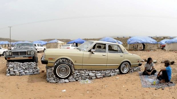Saudi youth sit next to their cars lifte