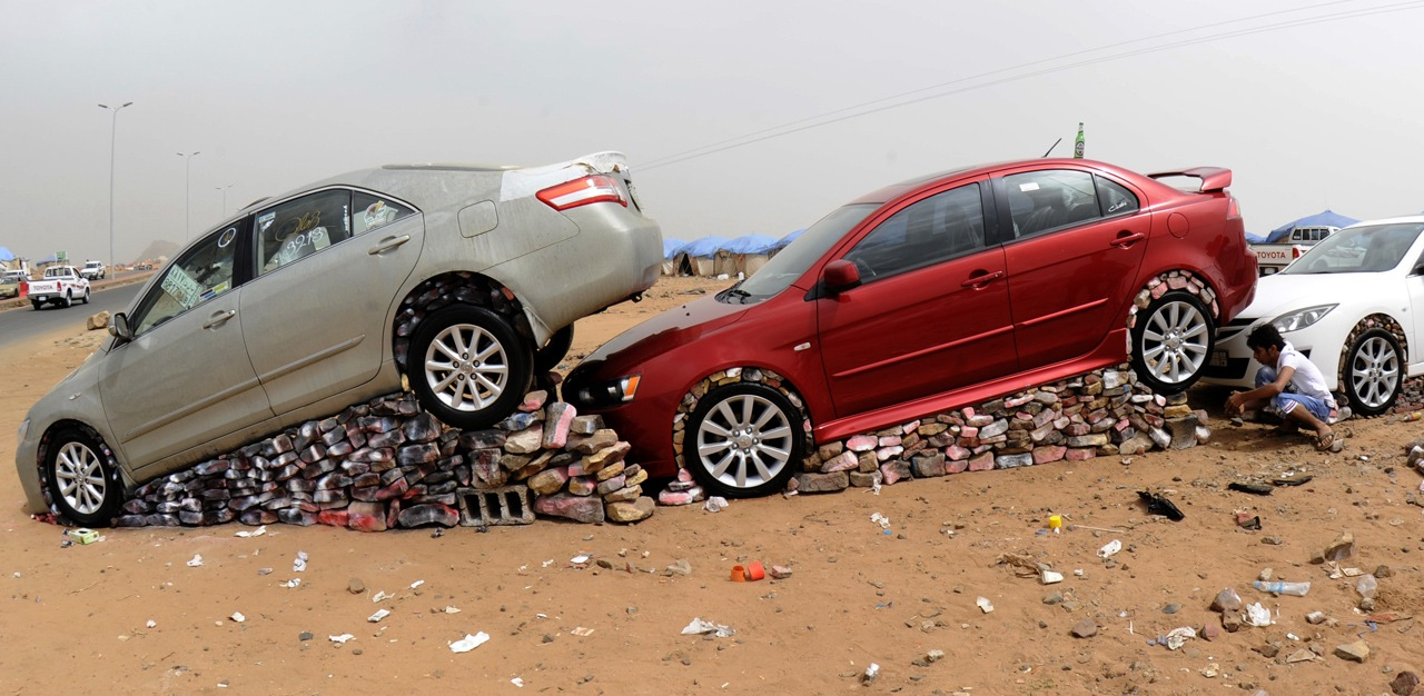 A Saudi youth lifts his car with stones
