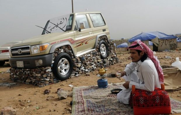 A Saudi youth sits nex to his sport util